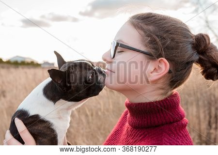 Teenage Smiling Girl In Glasses With Closed Eyes Holding A Boston Terrier Dog Licking Her Chin - Pro