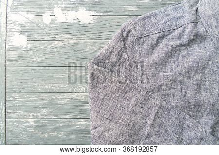 Men's Linen Shirt On Bright Wooden Background. Top View. Copy Space.