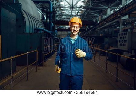 Smiling worker holds notebook, factory floor