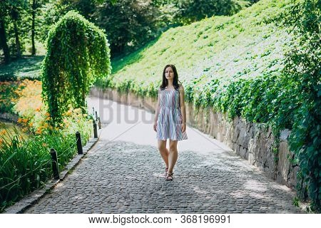 Sofia Park, Uman. The Girl Walks Along The Alleys Of The Park On A Sunny Day. Brunette Girl In A Whi