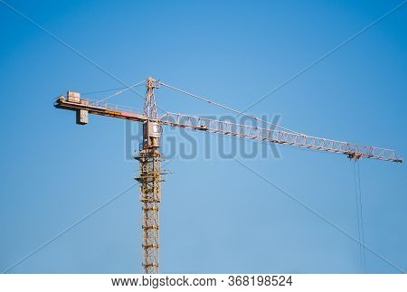 Construction Crane Tower On Blue Sky Background. Crane And Building Working Progress. Yellow Lifting