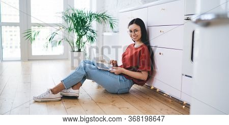 Pleased Freelance Adult Female Browsing Laptop At Home