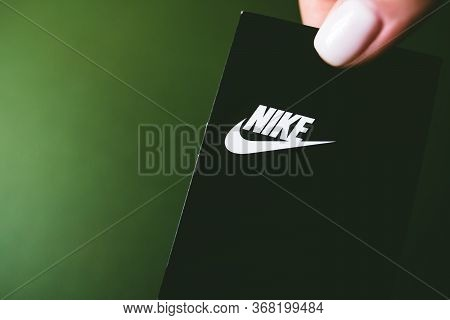 Closeup Of Nike Logo Label On Green Background. Nike Logo. Nike Is A Global Sports Clothes.