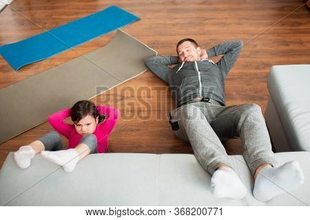 Father And Daughter Are Doing Abs Training At Home. Workout In The Apartment. Sports Training In The