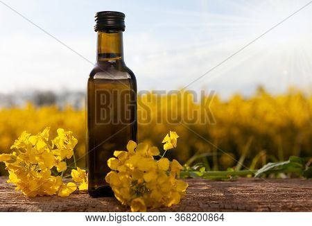 Rape Oil And Flower On Wooden Table With Nature Rape Field Background. Rapeseed Oil On Wooden Table