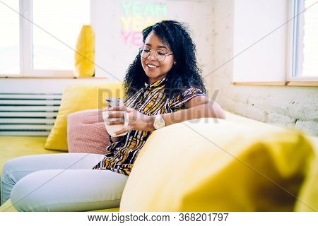 Cheerful Young Woman Drinking Coffee Browsing Smartphone