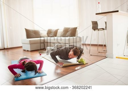 Father And Daughter Are Training At Home. Workout In The Apartment. Sports At Home. They Push Up On