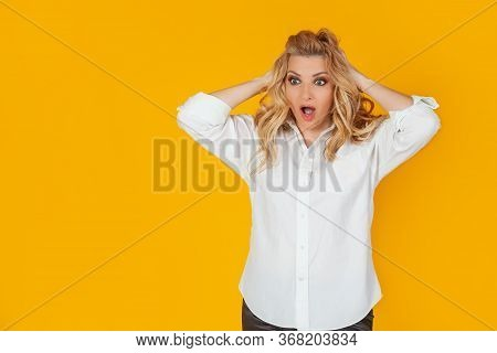 Portrait Of A Woman In A Panic With Her Hands Clutching Her Head, Excited And Looking Panicky Down,