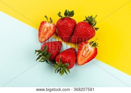A Top View Sliced Whole Strawberries Juicy Mellow On The Blue Yellow Floor