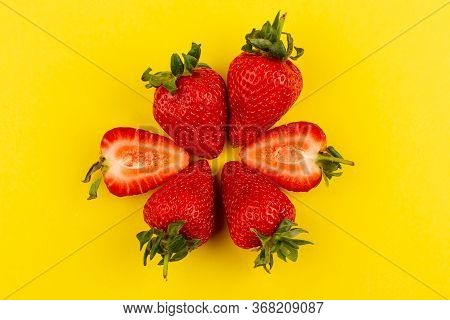 A Top View Strawberries Fresh Mellow Juicy Whole Sliced On The Yellow Floor