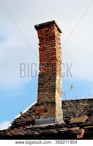 Crooked Leaning Old Chimney Made Of Dilapidated Cracked Red Bricks With Concrete Cap On Top Built On