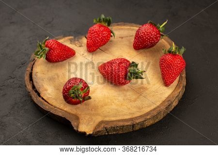 A Top View Red Strawberries Mellow Juicy Fresh On The Brown Desk On The Dark Background