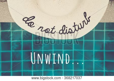 Straw Hat With Do Not Disturb Wording At The Pool Edge With Palm Reflections In The Water. Relax Vac