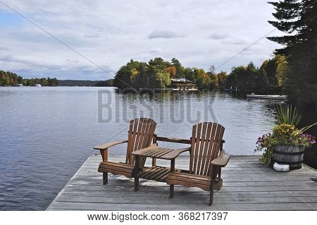 Two Muskoka Chairs Sitting On A Wood Dock Facing A Calm Lake. Across The Water Is A Cottage Nestled