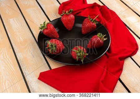 A Top View Red Strawberries Fresh Mellow Juicy Inside Black Plate On The Wooden Floor