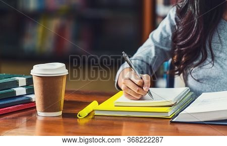 Closeup Asian Young Student Hand Writing Homework In Library Of University Or Colleague With Various