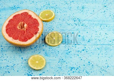 A Top View Grapefruits And Lemons Sliced Mellow Ripe On The Bright Blue Background