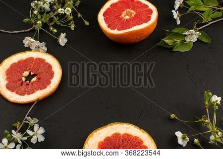 A Top View Grapefruits Sliced Juicy Mellow On The Dark Desk