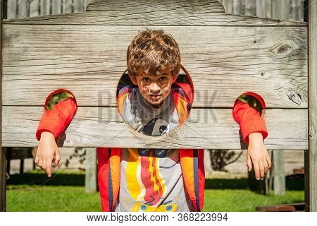 Boy With Head In Stocks At Tourist Attraction Maze, Youngster Tries Out The Out-fashioned Wooden Sto