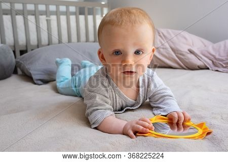 Little Baby Girl Holding Mirror And Looking At Camera. Cute Red-haired Toddler Surrounded Pillows An