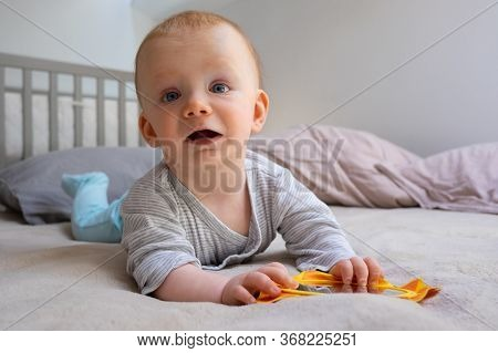 Cute Toddler Laying On Bed And Playing With Mirror. Red-haired Baby Girl Enjoying Being Inside. Self