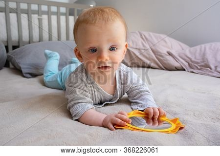 Red-haired Baby Girl Holding Mirror And Laying On Bed. Cute Thoughtful Toddler Surrounded Pillows An