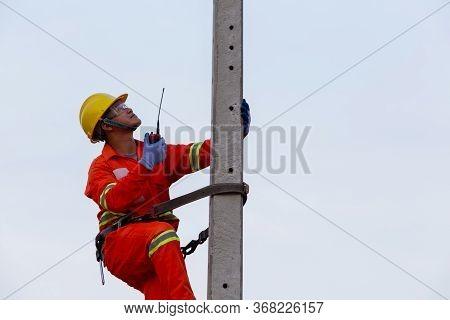 Electricians Work On High-voltage Electricity Poles, Along With Safety Equipment And Radio Communica