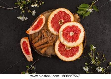 A Top View Sliced Grapefruit Fresh Mellow Juicy Ripe Along With Cinnamon On The Brown Desk And Grey