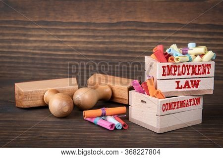 Employment Law And Compensation Concept. Colored Papr Scrolls In Wooden Boxes On Dark Wooden Backgro