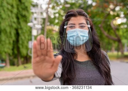 Young Indian Woman With Mask And Face Shield Showing Stop Gesture Outdoors