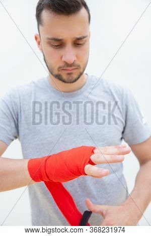 Concentrated Man Unwrapping Hand After Training. Guy With Bristle Removing Protection After Boxing O