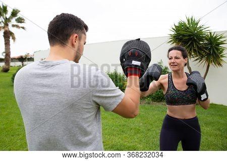 Active Middle Aged Woman Practicing Boxing With Trainer, Exercising Outdoors, Keeping Active Lifesty