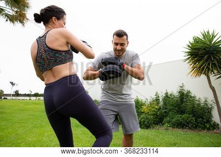 Couple Practicing Kickboxing Outdoors. Male Trainer Teaching Woman To Fight. Exercising Outdoors And