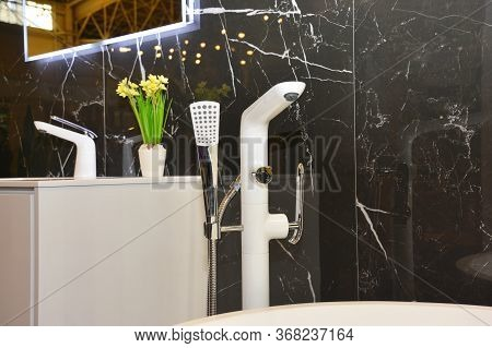 Installed White Bathroom Sink Faucet On A Sink Decorated With Flowers In A Vase And A White Freestan