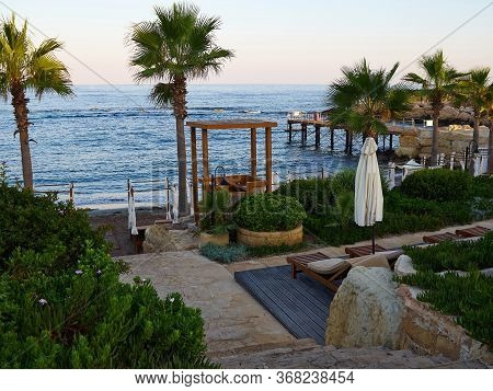 Sea Side Beach, Palm Trees And Sunbeds Of A Resort Hotel Great And Popular Summer Travel Vacation De
