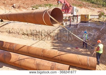 Workers Are Laying Metal Culverts Under The Highway Under Construction