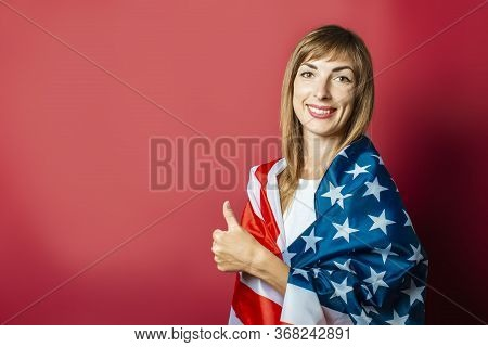 Young Girl Holds The Us Flag On A Pink Background. Concept Patriot, Holiday, Independence Day, Memor