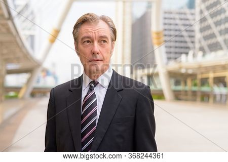 Mature Handsome Businessman In Suit Thinking At Skywalk Bridge In The City