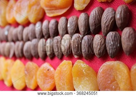 Almonds And Dried Apricots Lined With A Line On A Red Background. Almonds And Dried Apricots Close-u