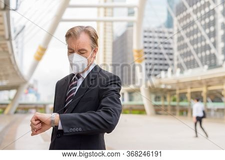 Mature Businessman With Mask Checking The Time At The Skywalk Bridge