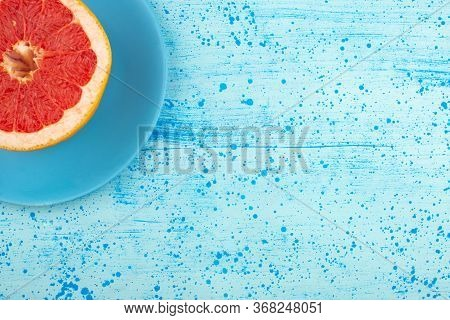 A Top View Sliced Grapefruit Juicy Mellow On The Blue Plate And Bright Blue Floor