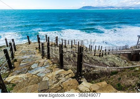 A Staircase With Stone Steps And Rope Handrails Leads Down To The Green Stormy Sea. On The Horizon M