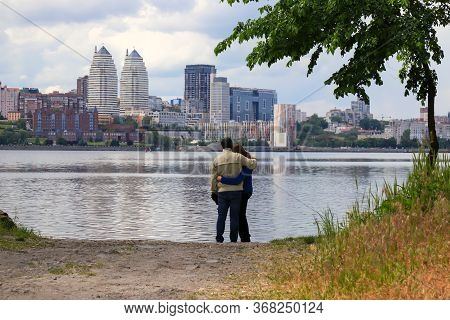 A Young Man And Girl Are Standing And Hugging On A Cloudy Morning On The Background Of Dnieper River