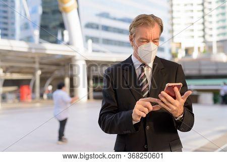 Mature Businessman With Mask Using Phone At The Skywalk Bridge