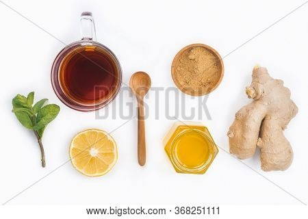 A Glass Cup Of Black Natural Tea With Ginger, Lemon, Mint And Honey Isolated On Wooden White Rustic