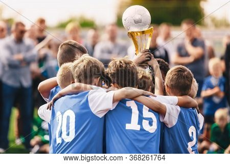 Junior Sport - Celebration. Boys In Sports Soccer Team Rising Up Golden Cup. Young Male Triumphant F