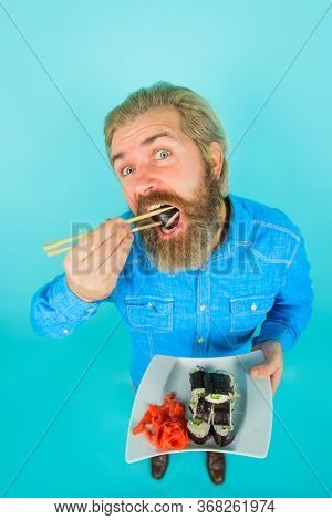 Bearded Man With Plate Of Sushiroll. Man Eating Sushi. Sushi. Man With Sushi On Chopstick. Japan. Su