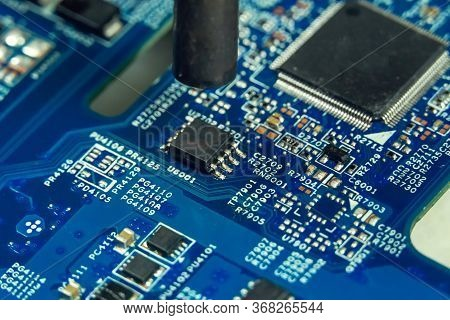 Electronics Engineer Repairs A Chip In The Workshop. Repairman Heats The Chipset Using Soldering Wit