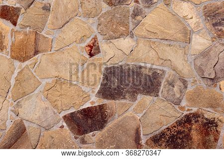 A Wall Built Of Wild Stone. Mosaic Of Stone. Strong Stone Wall. The Ancient Wall Of Stone.