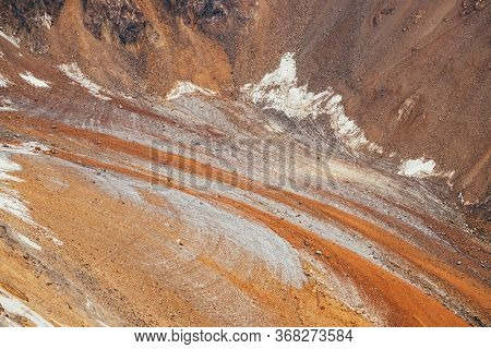 Unusual Glacier Tongue Covered With Stones Of Brown Orange Color In Sunlight. Scenic Nature Backgrou